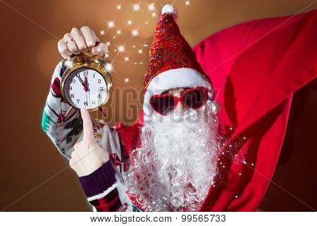 Man in Santa Claus costume with  clock