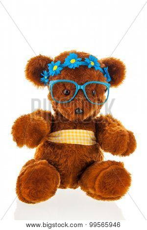 Funny stuffed bear with blue hair dress and glasses isolated over white background