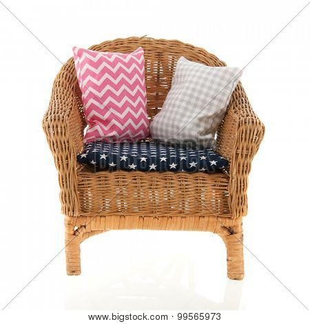 Wicker chair with colorful pillows
