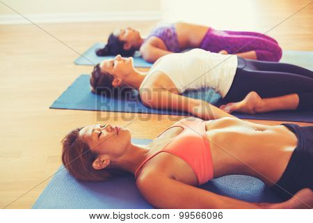 Young People Relaxing and Doing Yoga in Fitness Studio. Wellness and Healthy Lifestyle.