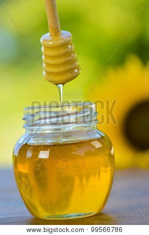 Honey Dripping Off A Honey Spoon Into A Glass Jar