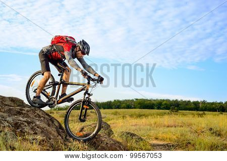 Cyclist Riding the Bike Down Rocky Hill. Extreme Sport Concept.
