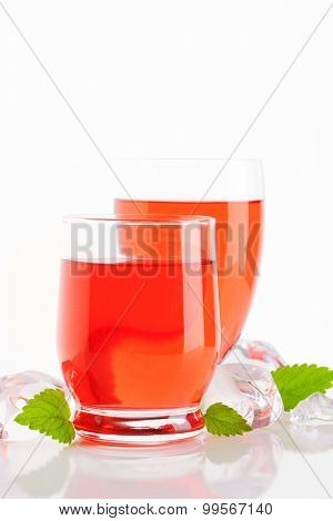 two glasses of fruit flavored drinks on white background