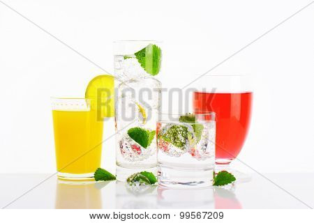 Glasses of water and fruit juices with mint and ice