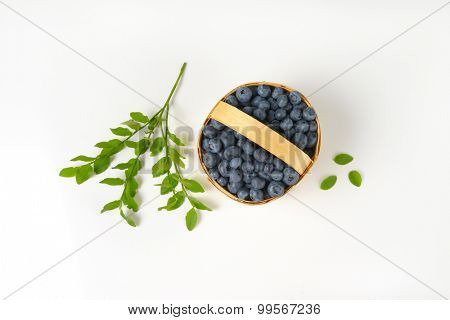 overhead view of straw basket with freshly picked blueberries
