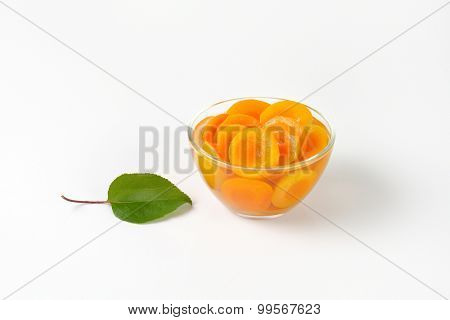 halved apricots in sweet infusion, served in the glass bowl