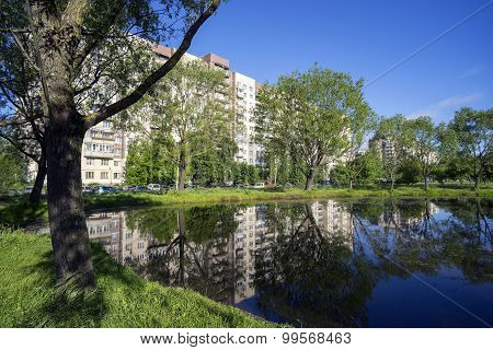 Apartment building with mirror reflection on the lake.