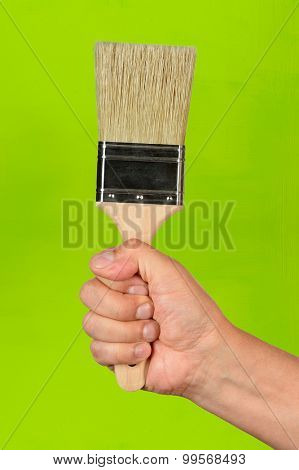 Hand holding paintbrush over green painted wall