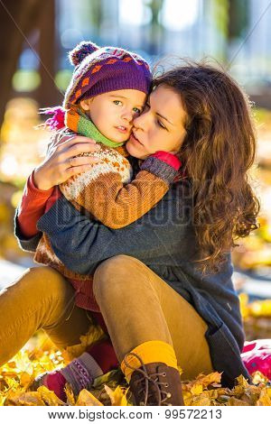 Little girl and her mother hugging in the autumn park