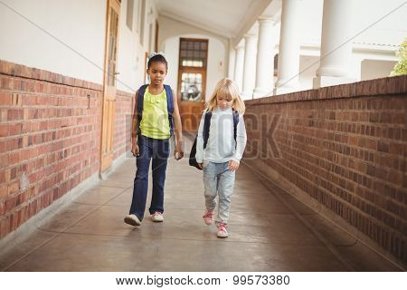 Cute pupils walking with schoolbags at corridor in school