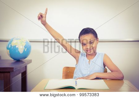 Smiling student with a rasied hand at the elementary school