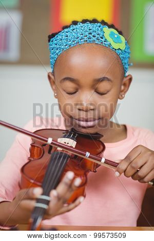 Focused pupil playing violin in a classroom in school