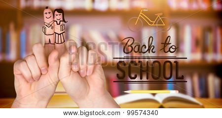 Fingers posed as students against books on desk in library