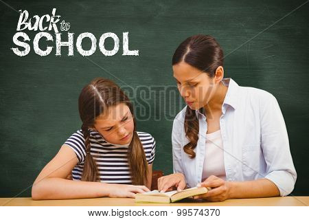 Teacher and girl reading book in library against green chalkboard