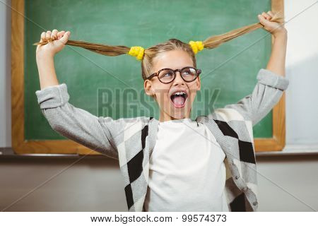 Cute pupil pulling her hair in a classroom in school