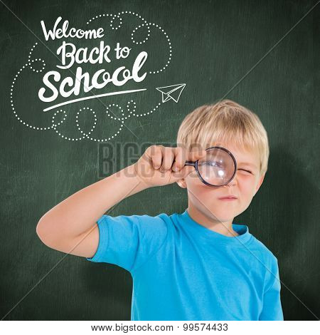 Cute boy looking through a magnifying glass against green chalkboard