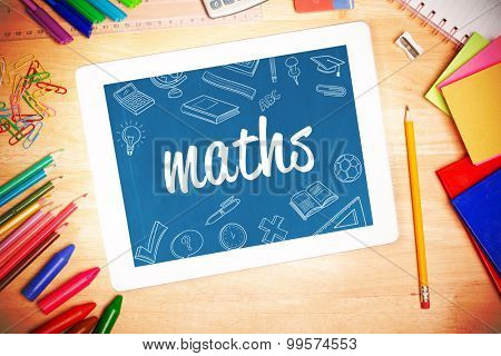 The word maths and school doodles against students desk with tablet pc