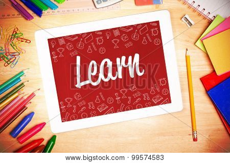 The word learn and school wallpaper against students desk with tablet pc