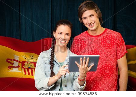 Smiling classmates with tablet pc against digitally generated spain flag rippling