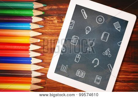 School icons against students desk with tablet pc