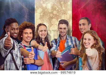 Smiling group of students doing thumbs up against france flag in grunge effect