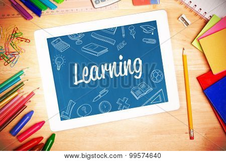 The word learning and school doodles against students desk with tablet pc