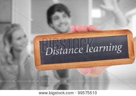 The word distance learning and hand showing chalkboard against colleagues envisioning an idea together