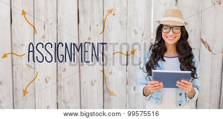 The word assignment against pretty hipster smiling at camera holding tablet