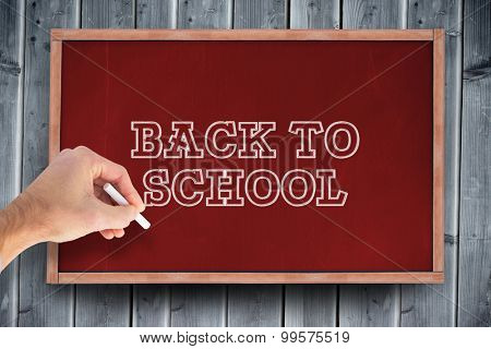 Hand writing with a white chalk against blackboard with copy space on wooden board