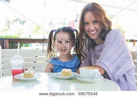 Mother and daughter enjoying cakes at cafe terrace on a sunny day