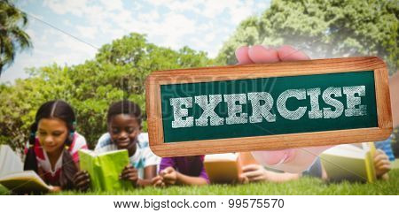The word exercise and hand showing chalkboard against children lying on grass and reading books