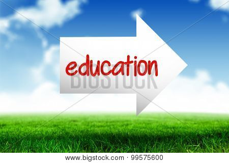 The word education and arrow against blue sky over green field