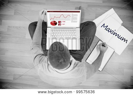 The word maximum and business interface with graphs and data against young creative businessman working on laptop