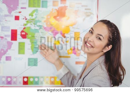 Portrait of pretty teacher showing world map in a classroom in school