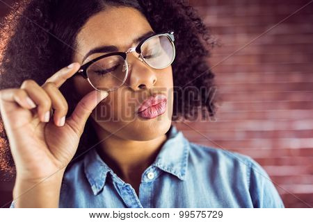 Attractive hipster sending air kiss against red brick background