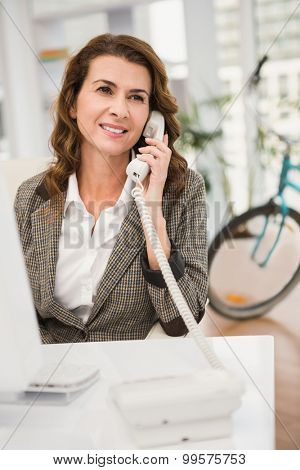 Smiling casual businesswoman phoning in the office