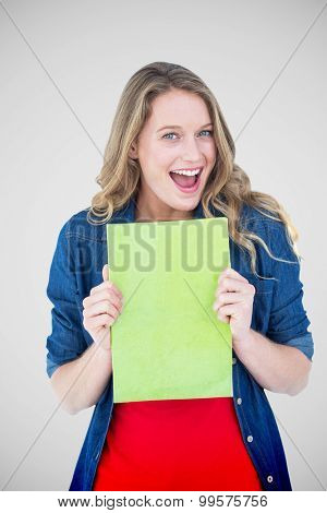 Smiling student holding notebook against grey vignette