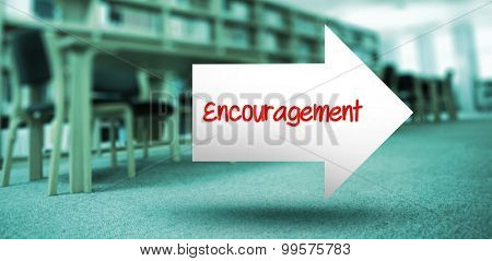 The word encouragement and arrow against volumes of books on bookshelf in library