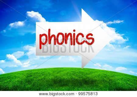 The word phonics and arrow against green hill under blue sky