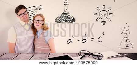 Happy geeky hipster couple with silly faces against desk