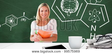 Mature student smiling against green chalkboard