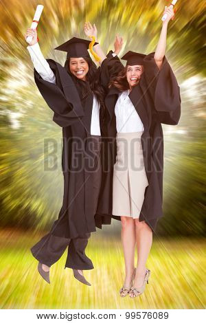 Full length of two women celebrating in the air against trees and meadow in the park