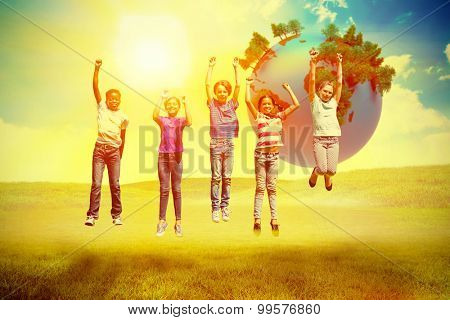Children jumping at park against blue sky over green field