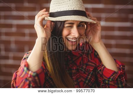 Beautiful hipster winking at camera on red brick background