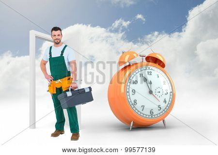 Smiling carpenter with toolbox against alarm clock counting down to twelve