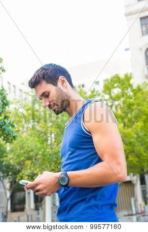 Handsome athlete using smartphone in the city