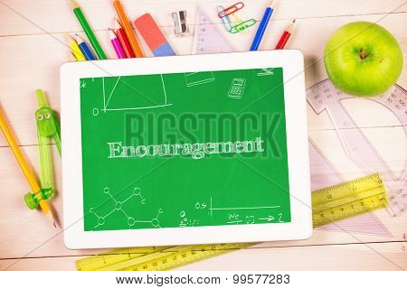 The word encouragement and math and science doodles against students desk with tablet pc