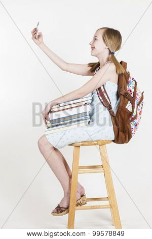 Portrait of friendly school girl student with backpack, sitting on a stool, holding notebooks and talking on a mobile phone