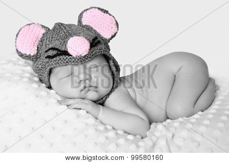 Newborn baby girl sleeping wearing a knitted mouse hat.