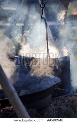 Steaming pot with food heated on the fire
